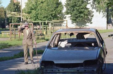 Rentner geht an einem Autowrack vorbei  Narva  Estland