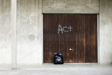 Garbage bag leaning against door graffitied with word act