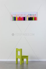 Child's chair and poster of colored pencils