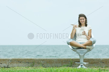 Teen girl sitting eating Chinese takeout food  ocean horizon in background