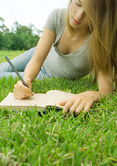 Young woman reclining in grass  writing in journal