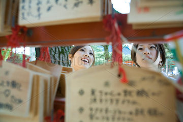 Young females looking at traditional Japanese ema wishes in Shinto shrine