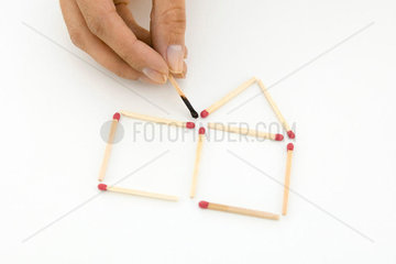 Hand arranging matches  holding one burnt match
