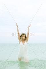 Woman standing knee deep in ocean  arms raised  smiling at camera