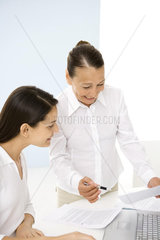 Senior woman working with younger colleague in office  smiling