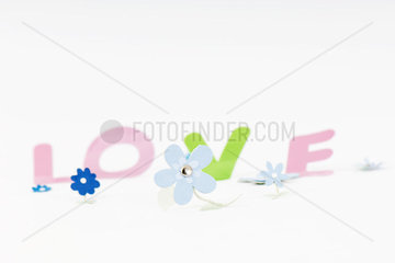 Paper flowers and letters spelling the word love