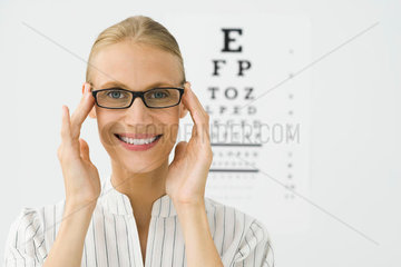 Young woman adjusting new glasses  eye chart in background  portrait