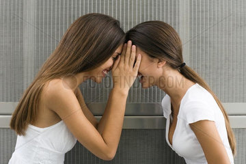Twin sisters face to face  touching foreheads  side view