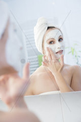 woman in bathroom with face masque