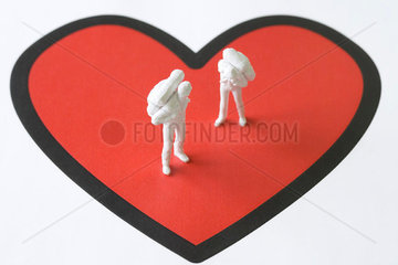 Miniature figures standing on large heart