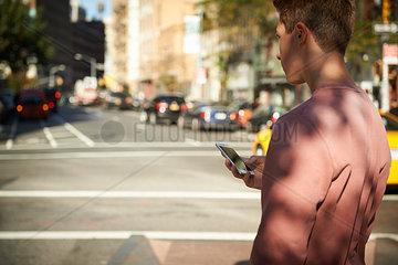 Junger Mann mit Smartphone in New York