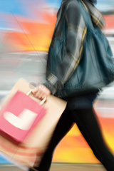 Shopper walking with shopping bags  blurred