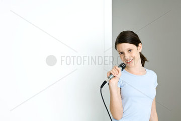 Preteen girl holding microphone  smiling at camera
