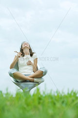 Teen girl sitting eating Chinese takeout  head back  low angle view