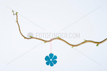 Flower ornament hanging from branch with new leaf buds