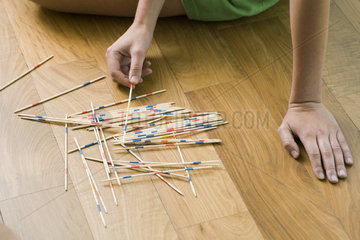 Female playing with pick up sticks on floor