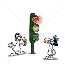 Woman standing at heart shaped streetlight as man waits