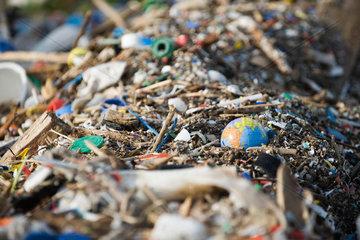 Globe in midst of landfill trash