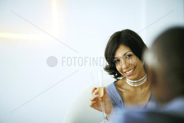 Woman holding champagne glass  smiling at camera  man in foreground