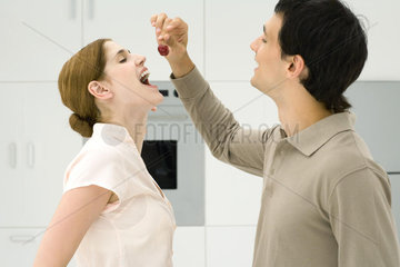 Couple standing together in kitchen  man feeding woman cherries  side view