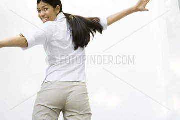 Woman smiling over shoulder at camera  arms spread  rear view