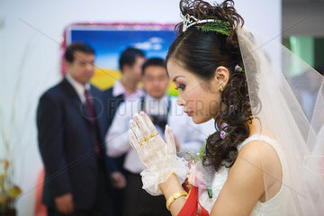Chinese wedding  bride's hands clasped in prayer  side view