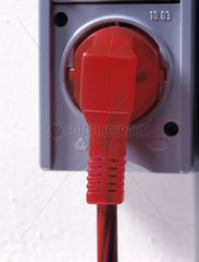 Roter Stecker in Steckdose