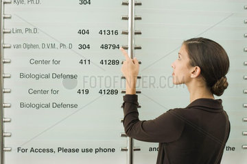 Teenage girl looking at building directory  pointing at number with finger