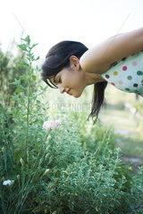Young woman bending over to smell flowers in garden