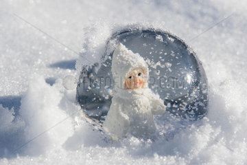 Snow globe with figurine of little girl in winter clothing sitting in snow