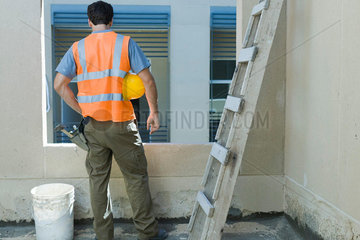 Construction worker with hand on hip looking out window  rear view