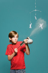 Boy spraying butterfly mobile with insecticide