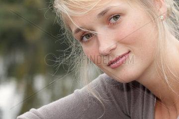 Blonde junge Frau  23 Jahre alt  schaut Keck in die Kamera (model released)