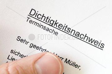 Hand haelt einen Brief mit Betreff Dichtigkeitsnachweis kuenftige gesetzliche Verordnung fuer Hausbesitzer
