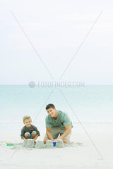 Father and son making sand castles at the beach  smiling at camera