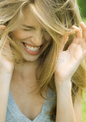 Young woman lowering head  shutting eyes and laughing with hands up