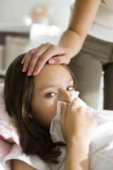 Girl with head cold  mother caressing forehead