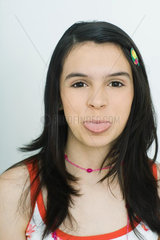 Teenage girl sticking out tongue  portrait