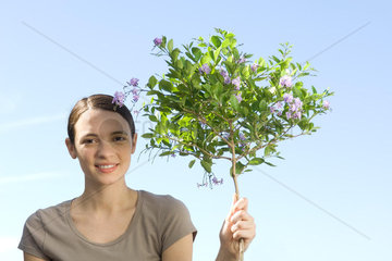Young woman holding slender trunk of flowering tree  smiling at camera