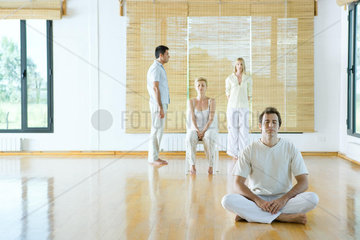 Four adults in various forms of meditation