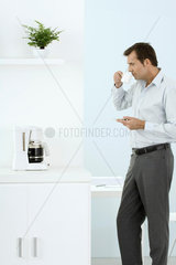 Man standing by coffee maker  taking a sip of coffee  holding saucer