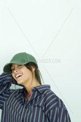 Teenage girl wearing button down shirt and cap  smiling at camera