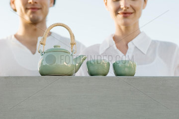 Teapot and tea cups sitting on ledge  cropped view of man and woman waiting nearby