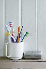 Toothbrushes in mug on shelf