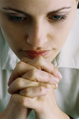 Woman with hands clasped in front of chin  close-up
