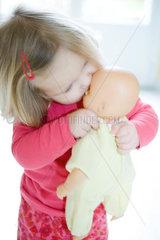 Blonde toddler girl kissing baby doll