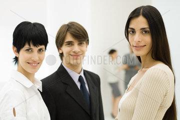 Three young professionals smiling at camera  close-up