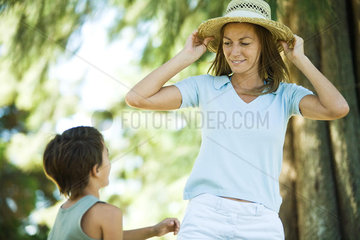 Mother and son  woman putting on straw hat