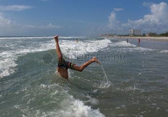 Cape Canaveral  USA  Junge macht am Strand einen Ueberschlag ins Meer