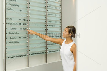 Woman looking at building directory  pointing at number